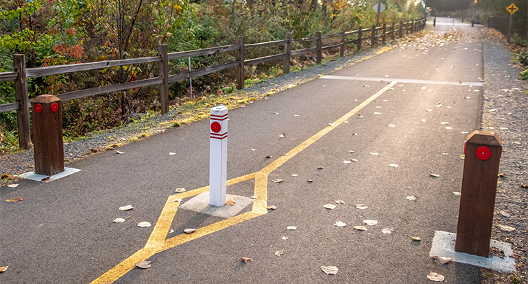 Photo shows single bollard on a paved pedstrian road.