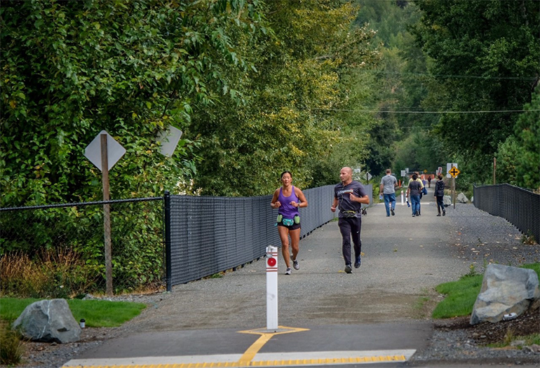 Two runners on the Eastrail trail pavement